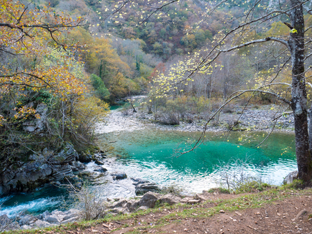 Crystal clear aquamarine waters of the Dobra mountain river in the Asturias in the North Spain. Autumn colors in the forest.