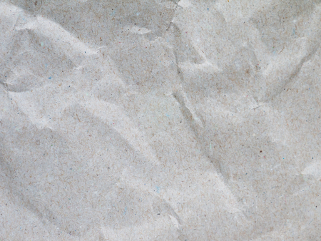 Crumpled recycled gray spotted packing paper with inclusions texture