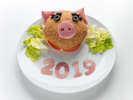 Childrens burger, lettuce salad and 2019 digits made of the pork ham as a symbol of new year. Animal chinese horoscope. Funny female piglet sandwich.