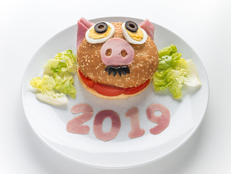 Kids burger, lettuce salad and 2019 digits made of the pork ham as a symbol of new year. Animal chinese horoscope.  Funny male piglet sandwich. Reklamní fotografie