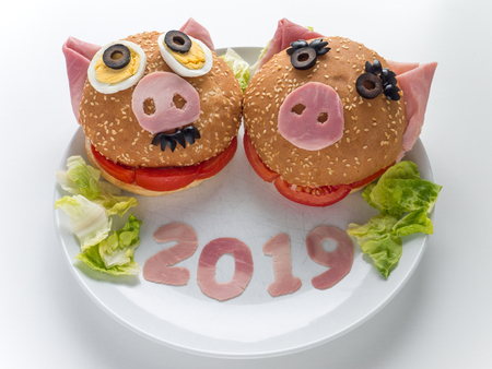 Funny piggies couple burgers, lettuce salad and 2019 digits made of the pork ham as a symbol of new year. Animal chinese horoscope.