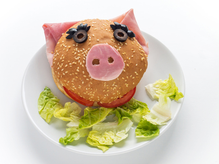 Hamburger and lettuce salad on the plate. Female piglet sandwich. Stock Photo