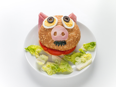Hamburger and lettuce salad on the plate. Male piglet sandwich. Stock Photo