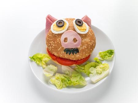 Hamburger and lettuce salad on the plate. Male piglet sandwich. Reklamní fotografie - 117093211