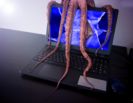 Computer virus concept. Laptop with broken screen seized by disgusting monster with long sticky tentacles.