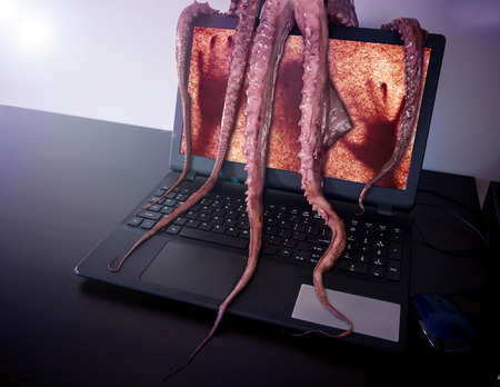 Computer virus concept. Notebook with man inside seized by disgusting monster with long sticky tentacles. Reklamní fotografie