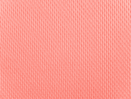 Coral polyester activewear knitted fabric texture. Color trend of the year 2019.