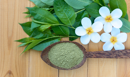 Henna powder in the coconut spoon and tiare flowers. Mhendi natural colorant Stock Photo