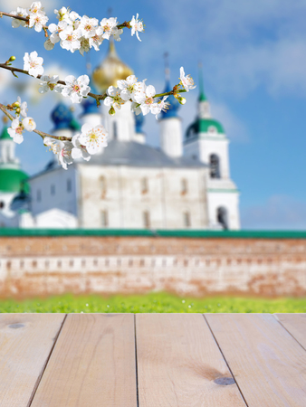Russian Orthodox Easter blurred church building bright sunny background. Rustic wooden planks table mockup. Spring blossom. Cherry tree branch with white flowers.