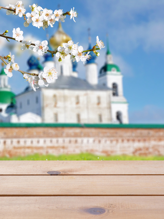 Rustic wooden planks table mockup. Russian Orthodox Easter blurred church building bright sunny background. Spring blossom. Cherry tree branch with white flowers. Reklamní fotografie - 117093780