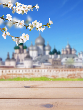 Wooden planks table mockup. Russian Orthodox Easter blurred church buildings bright sunny background. Spring blossom. Cherry tree branch with white flowers. Stock Photo