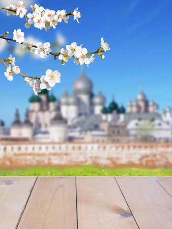 Russian Orthodox Easter blurred church buildings bright sunny background. Wooden planks table mockup. Spring blossom. Cherry tree branch with white flowers. Stock Photo - 117093794