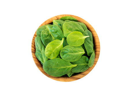 Spinach leaves in the olive wood bowl top view isolated on white. Green vegetable flay lay. Stock Photo