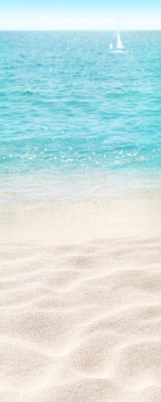 Beach blurred vertical background. Tropical island paradise. Sandy shore washing by the wave. Blue ocean water. 