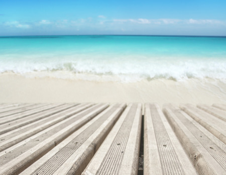 Wooden planks decking on the beach blurred background. Tropical island paradise. Sandy shore washing by the wave. Bright turquoise ocean water.  Dreams summer vacations destination. 版權商用圖片