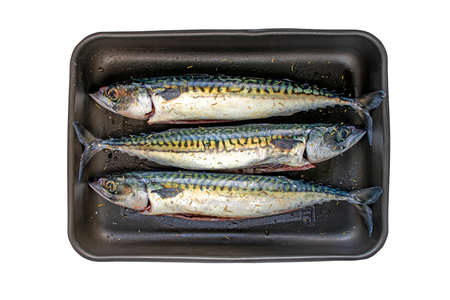 Mackerel fishes in the dark metallic roasting pan with nonstick coating. Food rich in omega 3.