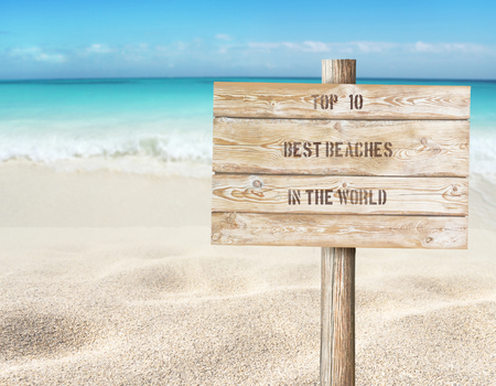 Top ten beaches in the world message on the wooden planks sign board on the beach blurred background.  Tropical island paradise. Sandy shore washing by the wave. Bright turquoise ocean water. 写真素材