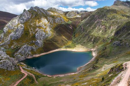 Cueva glacial lake in the Somiedo national park, Spain, Asturias. Saliencia mountain lakes. Top view from the viewpoint. Genista occidentalis yellow flowers. 版權商用圖片