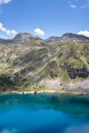 Mountain landscape near the Saliencia glacial lakes. Calabazosa lake in the Somiedo national park, Spain, Asturias. Turquoise crystal clear water. White snow spots.