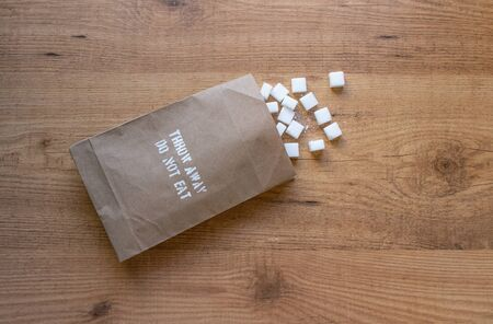 Sugar cubes in the paper pack on the table.