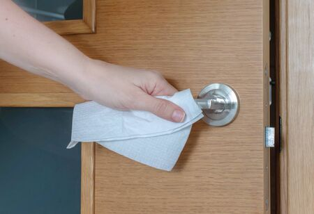 Hand touches a door handle through a paper serviette during a coronavirus epidemic. Transmission of the infection medical concept. Entry and exit safety protocol.