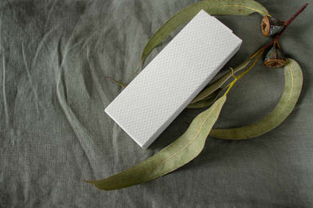 White textured paper box mockup and eucalyptus branch with leaves and fruits on the sage green linen fabric background. Stock fotó - 153100780