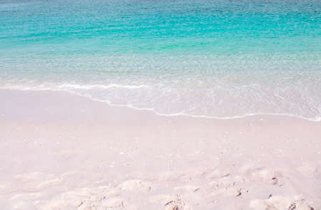 Pink sandy beach background. Crystal clear turquoise sea wave. Tropical summer paradise.