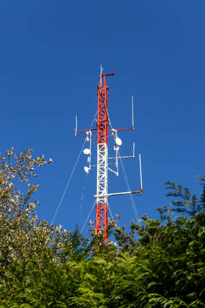 Red and white telecommunication mast or mobile tower with satellite antennas Reklamní fotografie