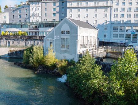 LOURDES, FRANCE - October 12, 2020: Hydroelectric power plant at the  Gave de Pau river, Lourdes, France. Renewable energy source.