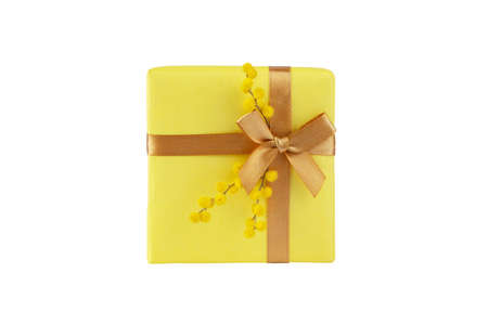 Yellow gift box with golden ribbon bow and mimosa fluffy flowers top view isolated on white. Spring holidays present.