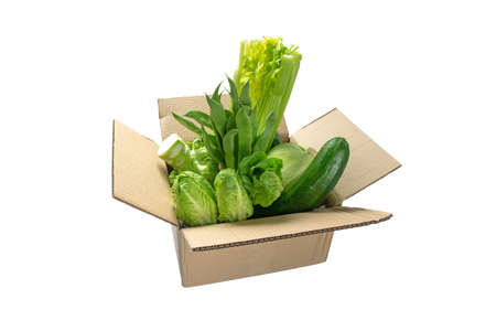 Green colored vegetables in the cardboard box isolated on white. Food purchase and delivery.