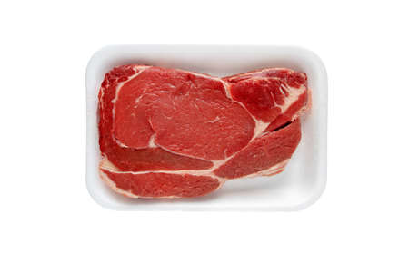 Juicy raw meat cut. Beef entrecote slice in the plastic foam tray isolated on white top view. 写真素材
