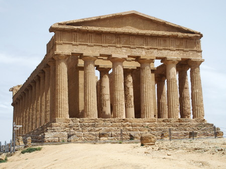 Famous ancient greek temple of Concordia in Valley of the Temples in AGRIGENTO city in SICILY landscape in ITALY with cloudy sky in warm sunny spring day - facade, EUROPE, MAY. Stock Photo