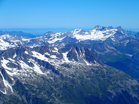 Alpine mountains range landscape in beauty French, Italian and Swiss ALPS seen from Aiguille du Midi at CHAMONIX MONT BLANC in FRANCE with clear blue sky in 2016 warm sunny summer day, Europe on July. Stock Photo