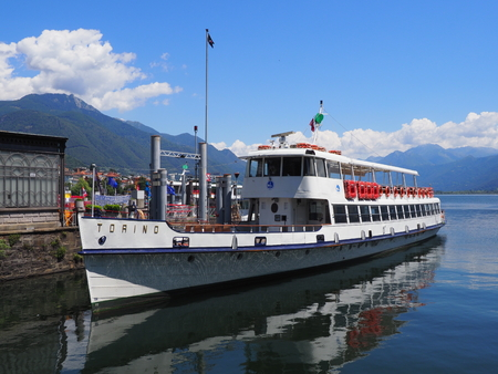 Paddle-wheel steam boat moored ready to cruise at promenade on alpine Maggiore Lake in Locarno at Switzerland
