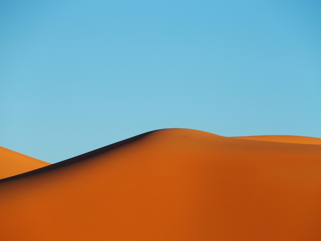 Peak of ERG CHEBBI dunes near MERZOUGA with landscapes of sandy desert formations in southeastern MOROCCO near border with ALGIERIA, clear blue sky in 2017 warm sunny winter day, Africa on February.