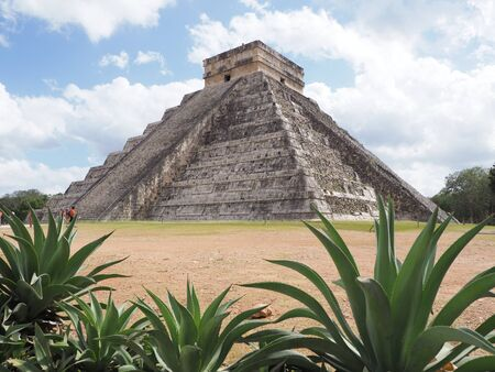 Pyramid and agaves in Chichen Itza mayan town in Mexico, ruins at archaeological sites landscapes with cloudy blue sky in 2018 warm sunny winter day, North America on February.