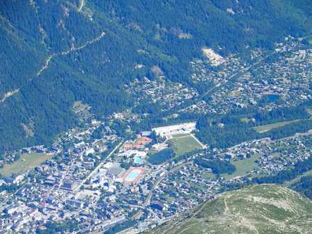 CHAMONIX MONT BLANC village in valley seen from AIGUILLE du MIDI peak at highest alpine mountains range in french ALPS landscapes in FRANCE in 2016 warm sunny summer day, aerial view, Europe on July.