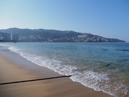 Beauty panorama of sandy beach at bay of ACAPULCO city in Mexico and waves of Pacific Ocean with black line and clear blue sky in 2018 hot sunny winter day, North America on March. Banco de Imagens