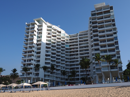 White hotel building on beauty sandy beach at bay of Pacific Ocean at ACAPULCO city in Mexico with palm trees Editorial
