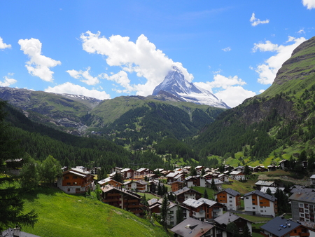 Scenic view on swiss Zermatt village with housing estate and Matterhorn mount in Switzerland at alpine mountains range landscapes with cloudy blue sky in 2017 warm sunny summer day, Europe on July.