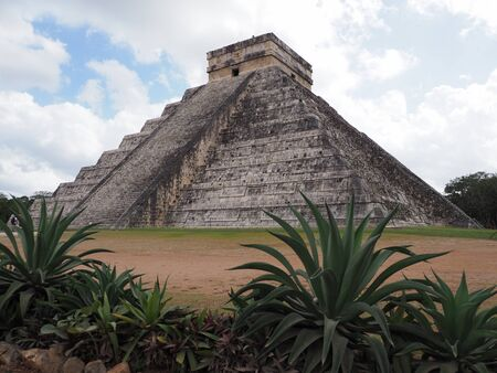 Pyramid and agaves in Chichen Itza mayan town at Mexico, ruins at archaeological sites landscapes with cloudy blue sky in 2018 warm sunny winter day, North America on February. Stock Photo