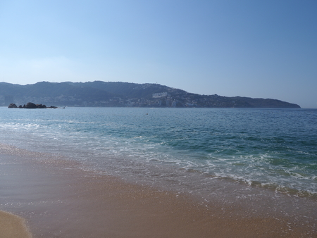 Panorama of beauty sandy beach at bay of ACAPULCO city in Mexico and waves of Pacific Ocean with clear blue sky in 2018 hot sunny winter day, North America on March. Banco de Imagens