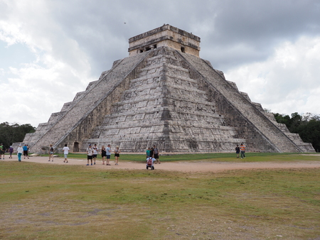CHICHEN ITZA, MEXICO NORTH AMERICA on FEBRUARY 2018: Scenic pyramid and tourists in mayan town, ruins at archaeological sites landscapes with cloudy blue sky in warm sunny winter day. Editorial