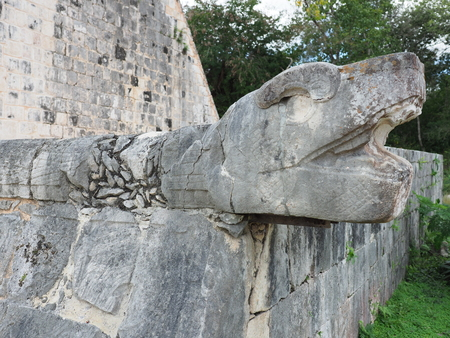Sculpted stony snake head at mayan ruins of great ball court building in Chichen Itza city in Mexico, largest and most impressive site at country in 2018 warm sunny day, North America on February.