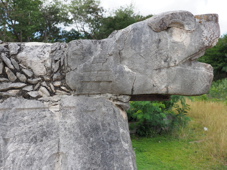 Sculpted stony snake head at mayan ruins of great ball court building in Chichen Itza city in Mexico, largest and most impressive site in country in 2018 warm sunny day, North America on February