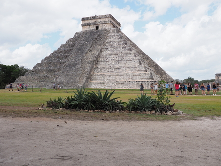 CHICHEN ITZA, MEXICO NORTH AMERICA on FEBRUARY 2018: View of ancient pyramid and agaves in mayan town, ruins at archaeological sites landscapes, tourists and cloudy blue sky in warm sunny winter day. Editorial