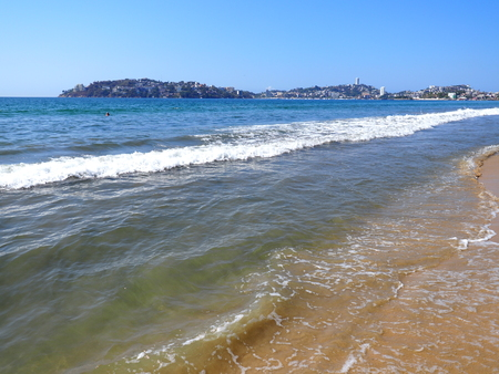 Beauty colorful mexican landscapes of sandy beach at bay of ACAPULCO city in Mexico and waves of Pacific Ocean with clear blue sky in 2018 hot sunny winter day, North America on March.