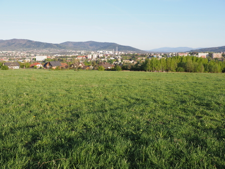 Panoramic cityscape landscapes of european Bielsko-Biala city and countryside of grassy field at Beskid Mountains in POLAND with green plants, clear blue sky in 2018 warm sunny spring day on June
