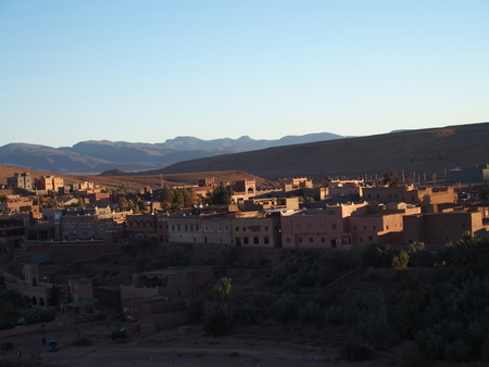 Kasbah Ait Ben Haddou or Benhaddou fortified city with green exotic palm trees at oasis on african Atlas Mountains range landscapes of Morocco, clear blue sky in 2017 warm sunny winter day, February